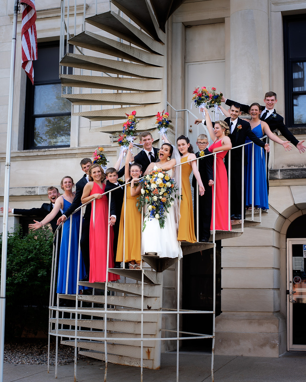 bride and groom celebrating with their wedding party on the spiral staircase in Seward, Nebraska