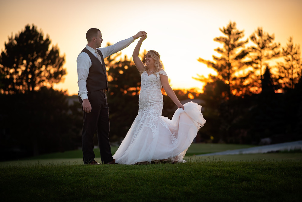 groom twirling bride on golf course at sunset at Wilderness Ridge
