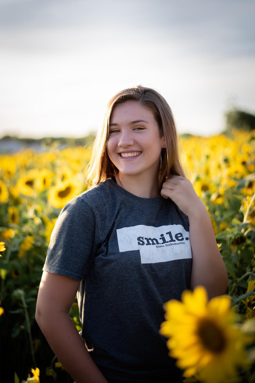 teen smiling while in a sunflower field in Nelson Produce in Valley, Nebraska