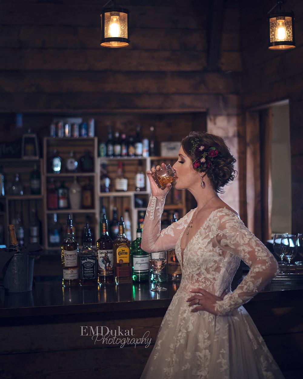 bride drinking whiskey at Ackerhurst Dairy Barn in Bennington, Nebraska