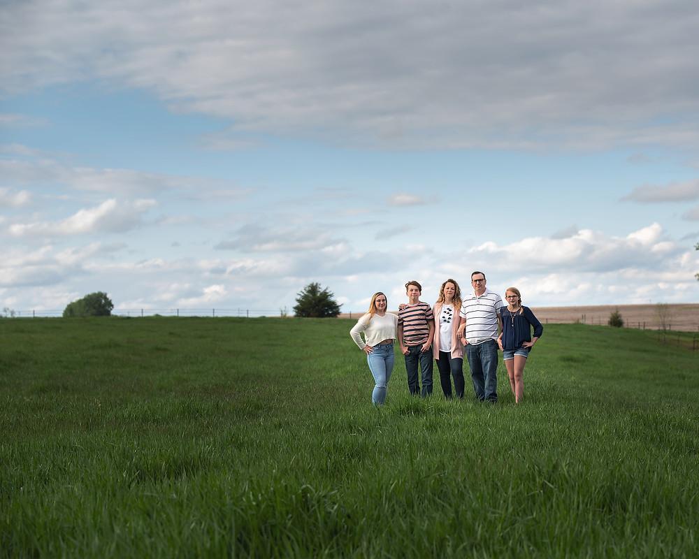 family standing in grassy field for Spring portraits in Gretna, NE