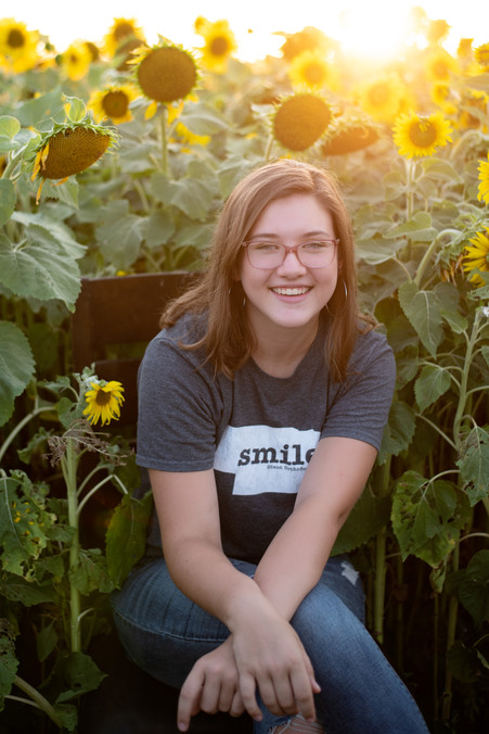 close up of girl smiling in sunflower field at Nelson Produce in Valley, Nebraska