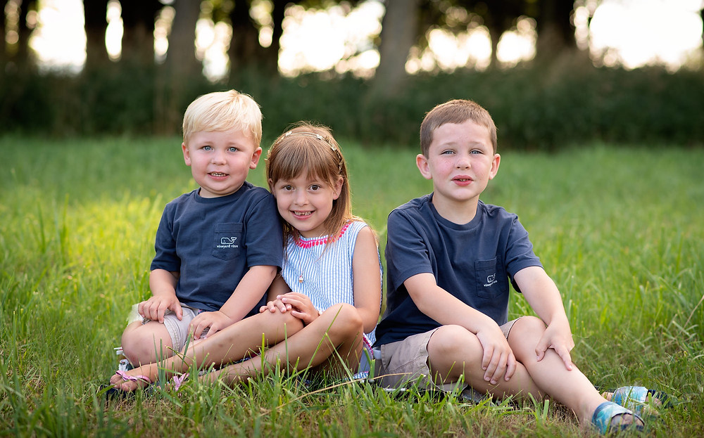siblings sitting in a grassy field at sunset in Gretna, NE