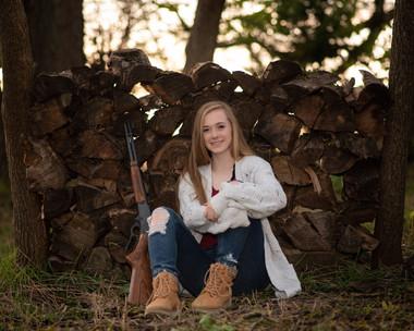 senior girl poses near log pile in Gretna, Nebraska