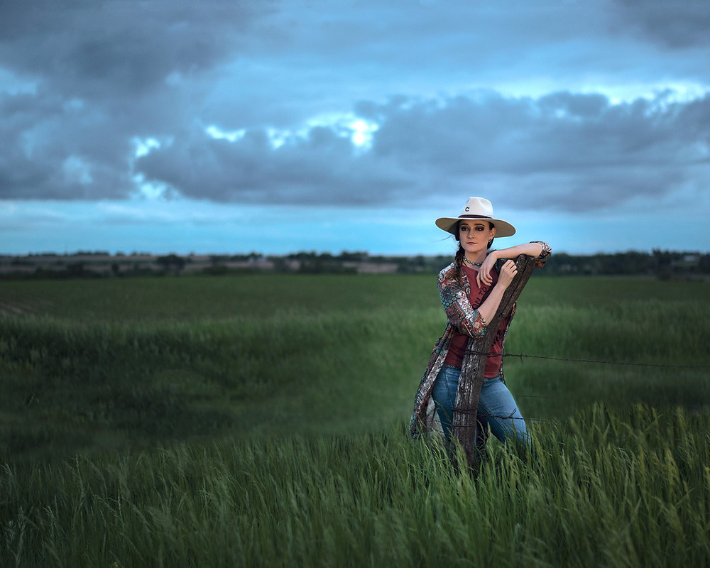 cowgirl leaning on fence post in a grassy field with thunderstorm brewing behind her