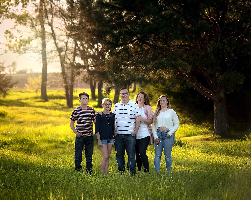 Staley Family standing in grass field at golden hour for family portraits in Gretna, Nebraska