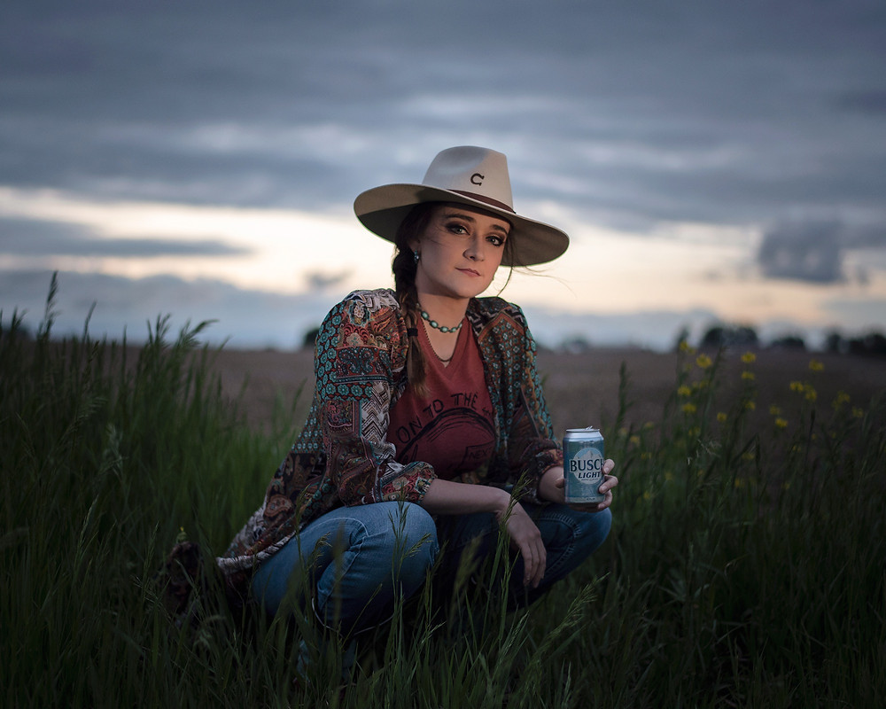 boho cowgirl wearing a Charlie 1Horse hat holding a Bush Light in the field at sunset
