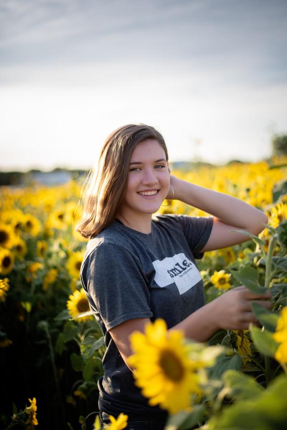teen posing in Nelson Produce sunflower field in Valley, Nebraska