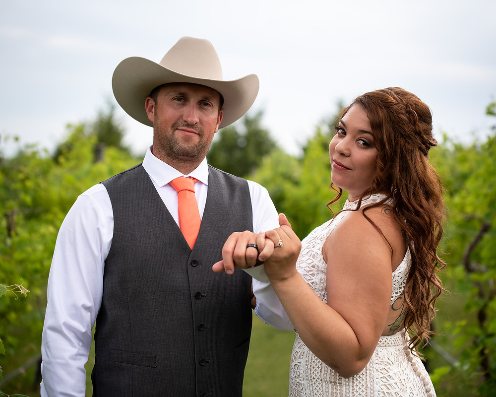 cowboy groom & bride pinky promise in vineyard at Country Pines in Lincoln