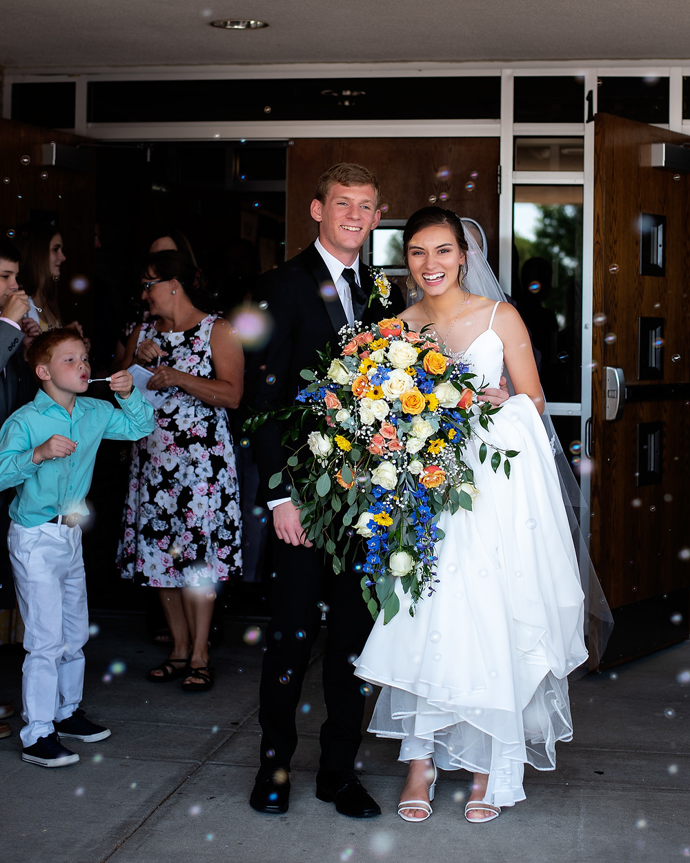 newly husband & wife walk out of church into a tunnel of family blowing bubbles