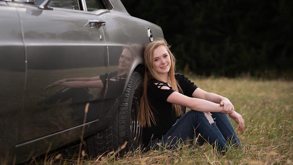 senior girl leaning against classic car in a field in Gretna, Nebraska