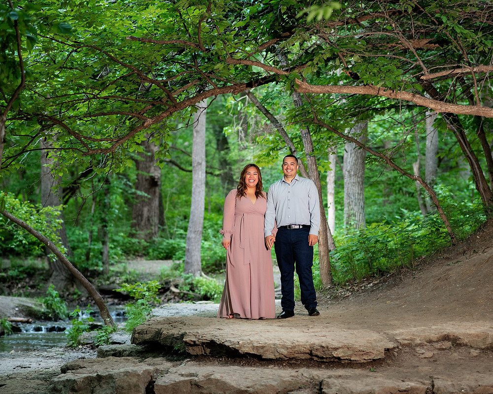 Engaged couple stands under tree by Stone Creek Falls waterfall