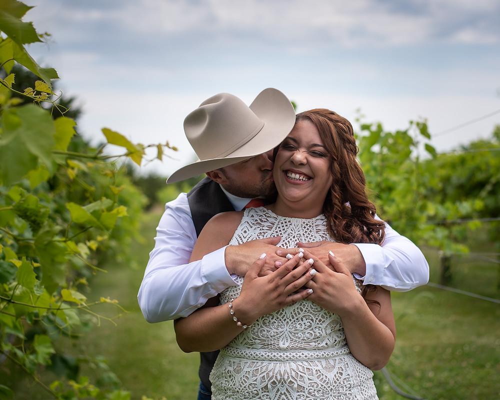 groom kissing bride on cheek in vineyard in Lincoln, NE