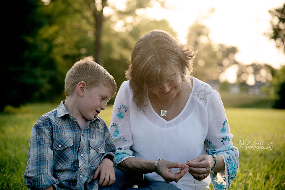 Grandson picking dandelions with grandmother in Springfield, NE at sunset
