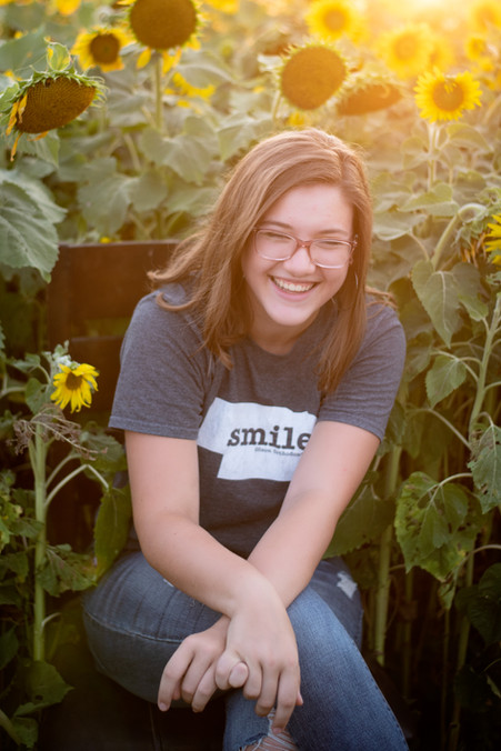 teen laughing in sunflower field at Nelson Produce in Valley, Nebraska