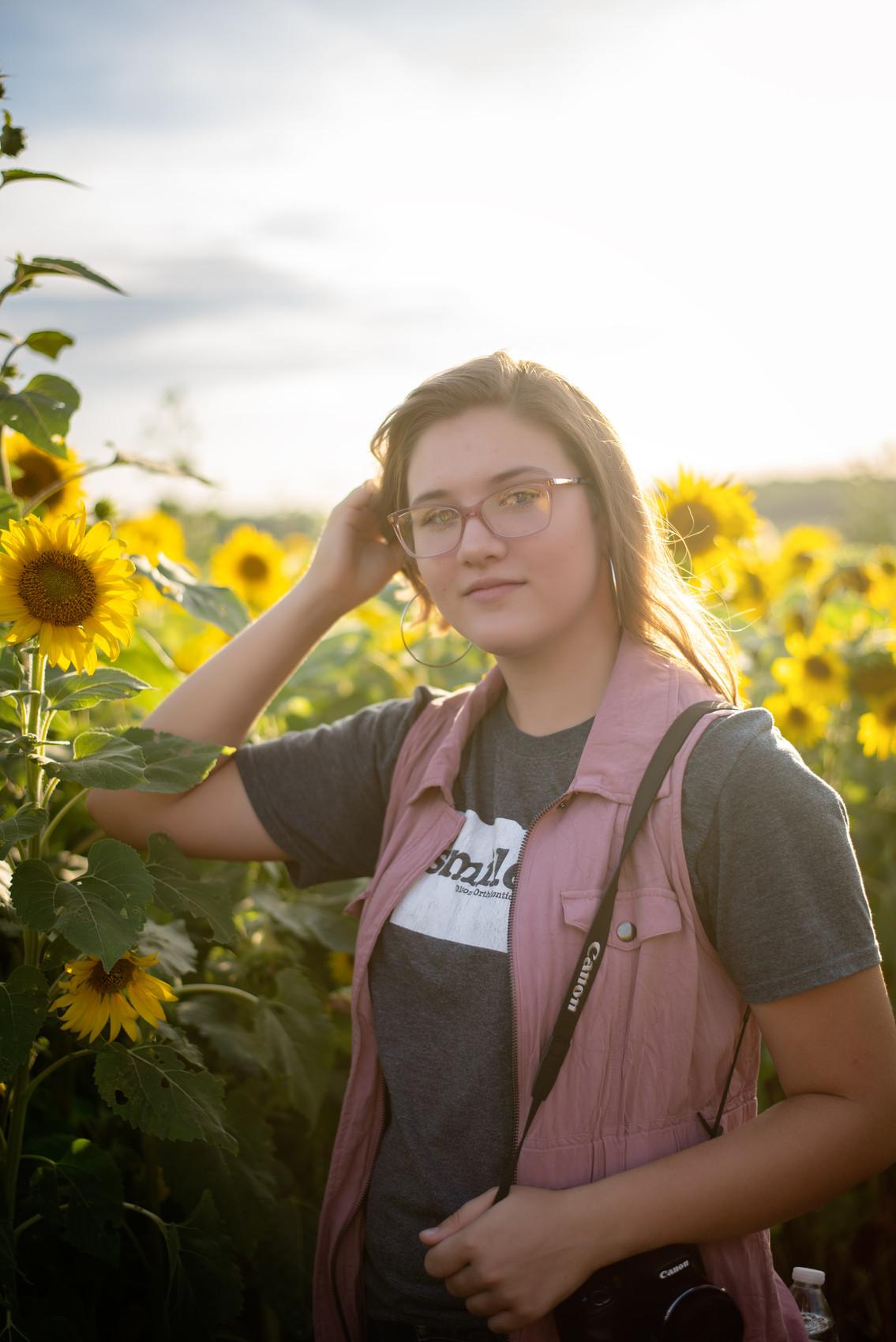 teen posing in sunflower field at Nelson Produce in Valley, NE
