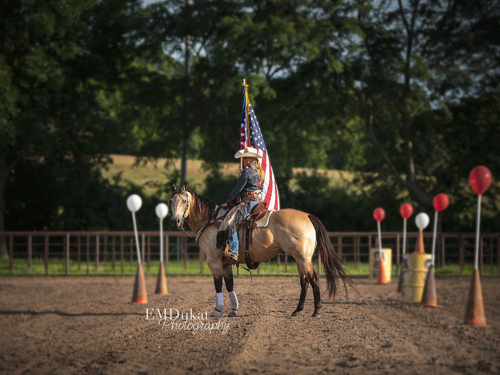 cowgirl and horse holding flag at mounted shooting competition in Elkhorn, NE