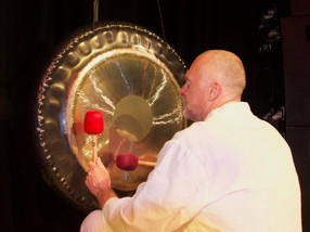 Paul Dane playing the gongs on stage