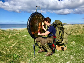 Hiker playing the gong in the Outer Hebrides