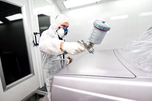 worker painting a grey car in a special