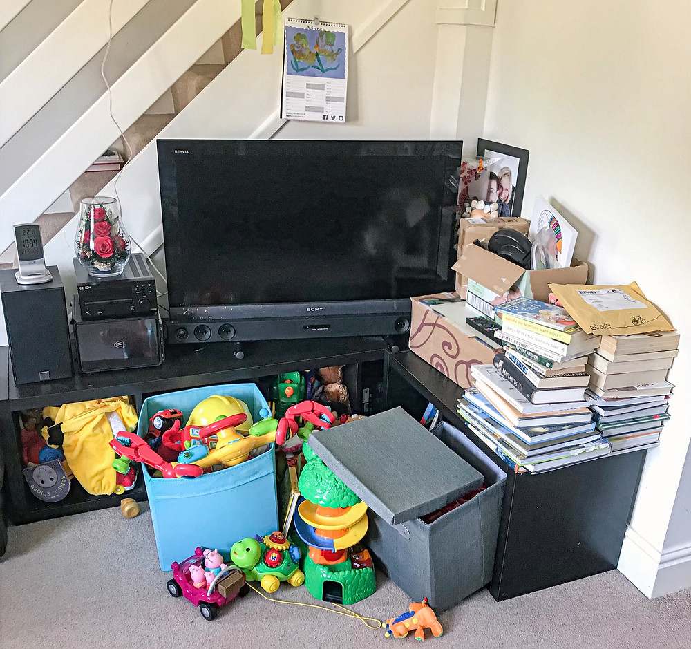 Cluttered TV unit paperwork, books and toys