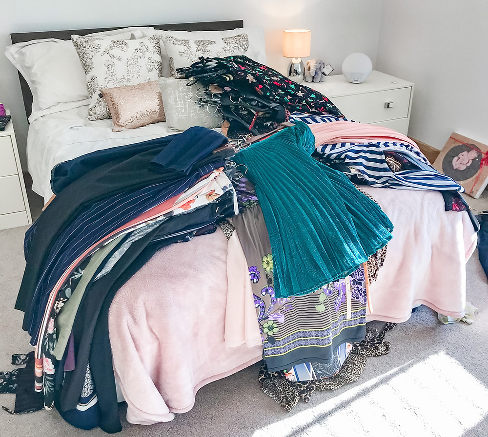 KonMari Method Power of the Pile - Clothes piled on a bed to check if they spark joy