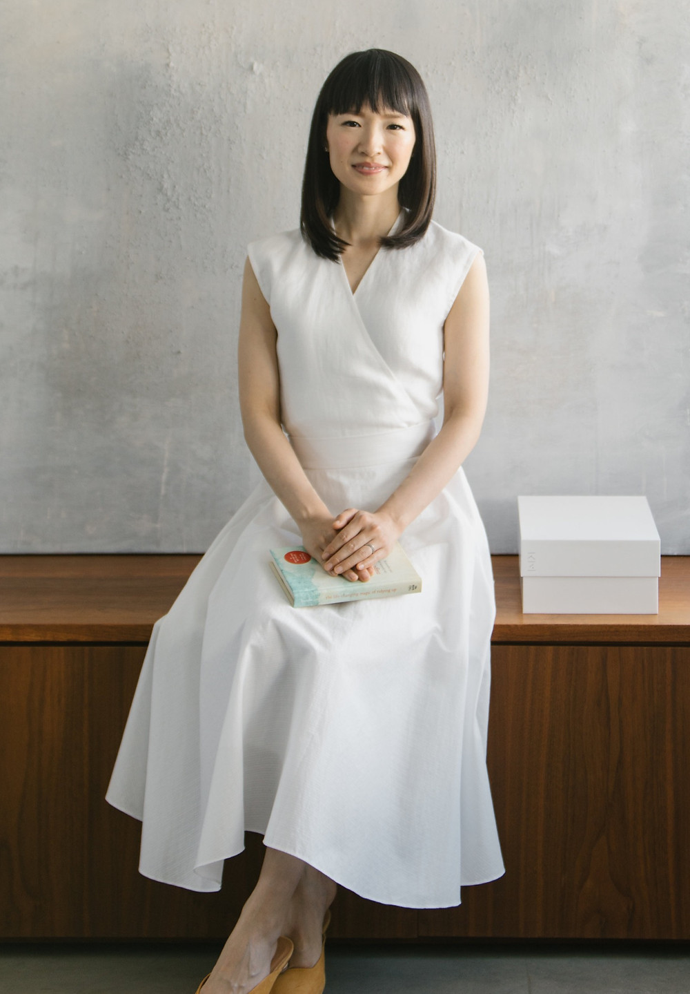 Japanese organising Expert Marie Kondo holding her book, The Life Changing Magic of Tidying