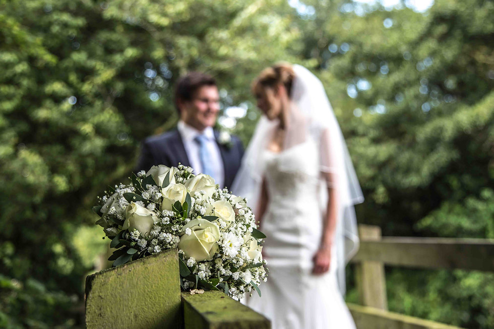 flowers with bride and groom in the background