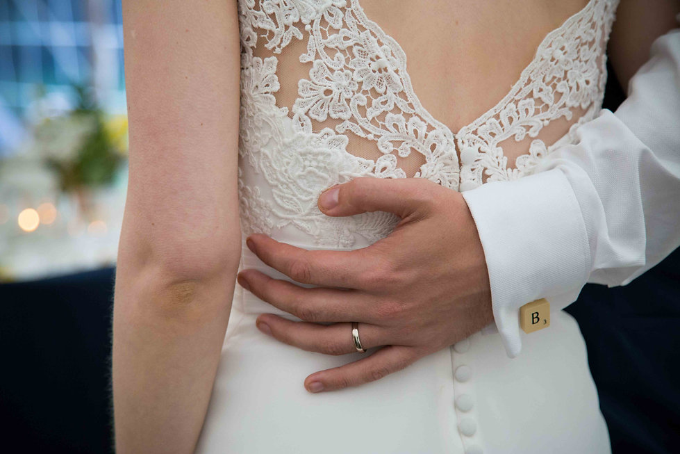 Grooms hand on back wth ring