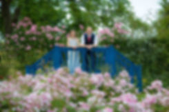 bride and groom on bridge with flowers