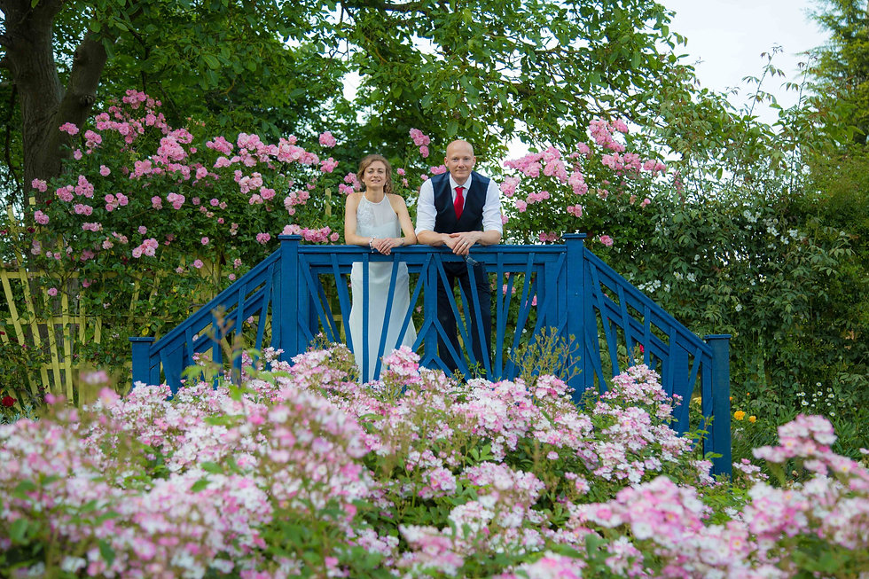 bride and groom on bridge with flowers