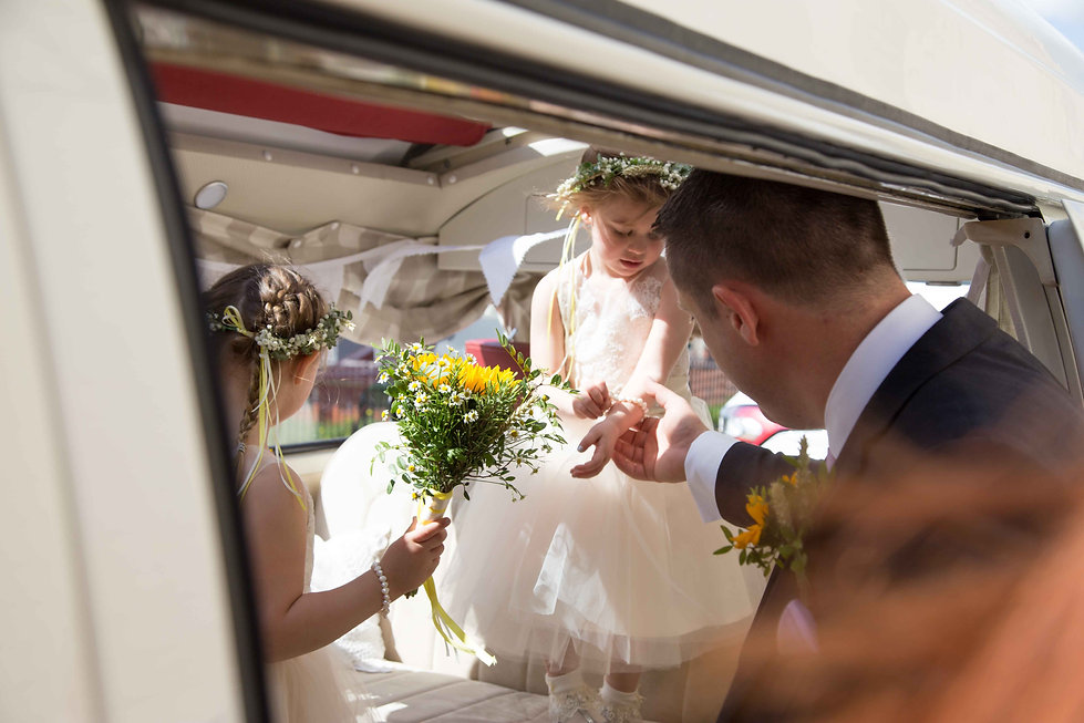 A bridesmaid child being helped out of the car at the Castle venue