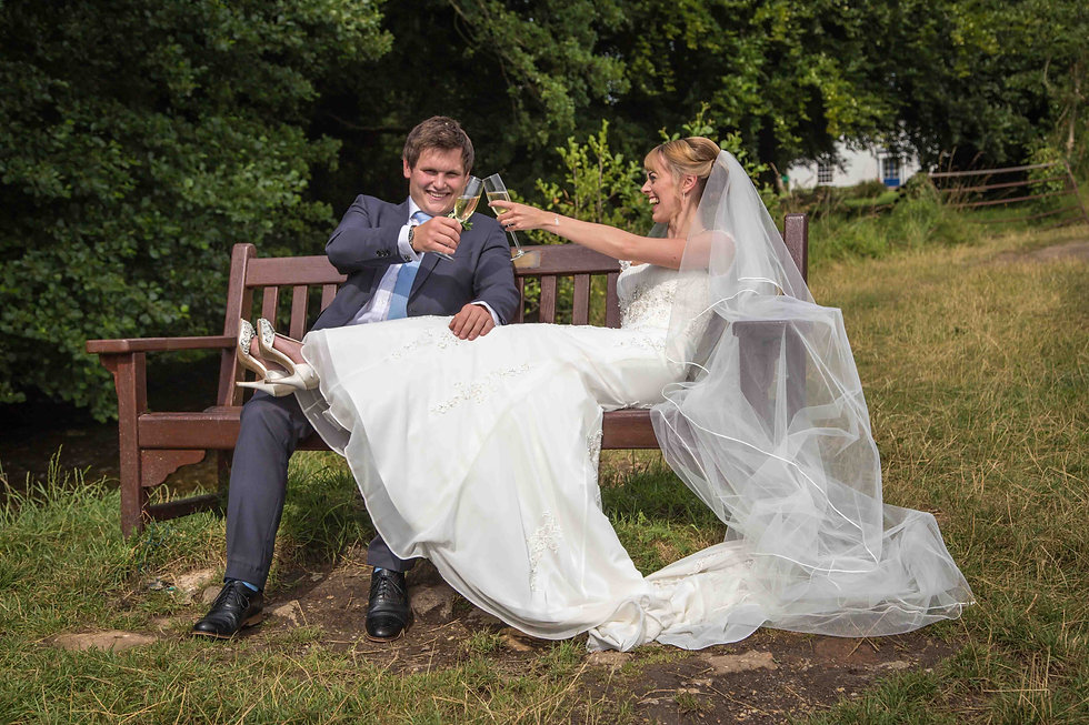 The bride and groom drinking on bench