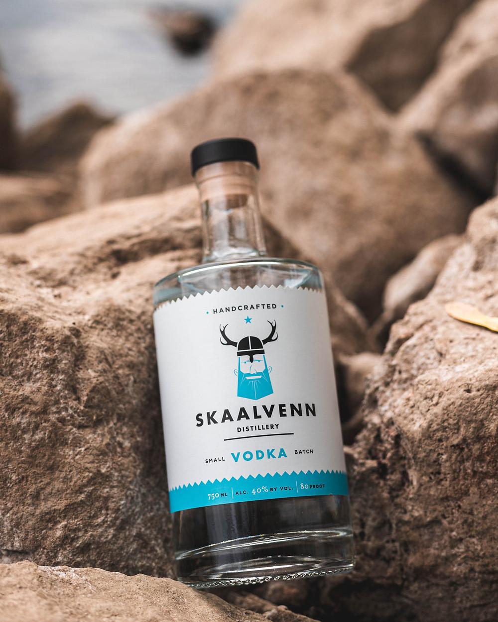 Skaalvenn Vodka sitting on some rocks by the river