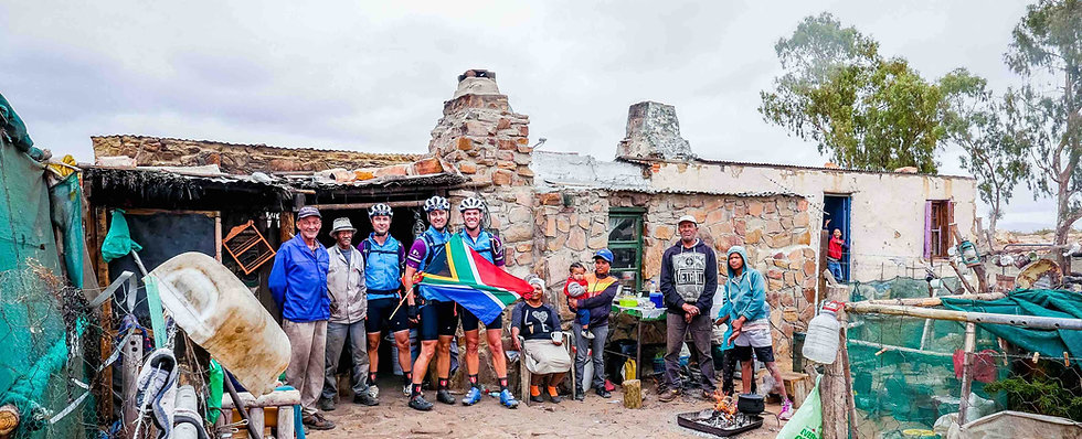 Cyclist with flag at rural house for Miles for a Million