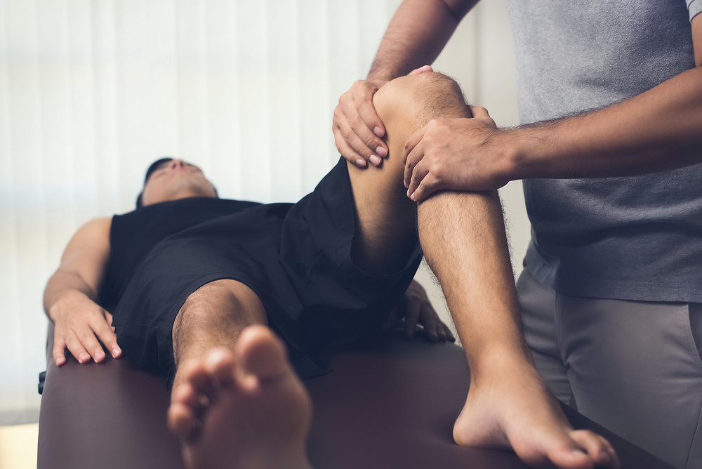 injured athlete getting assistance from a therapist
