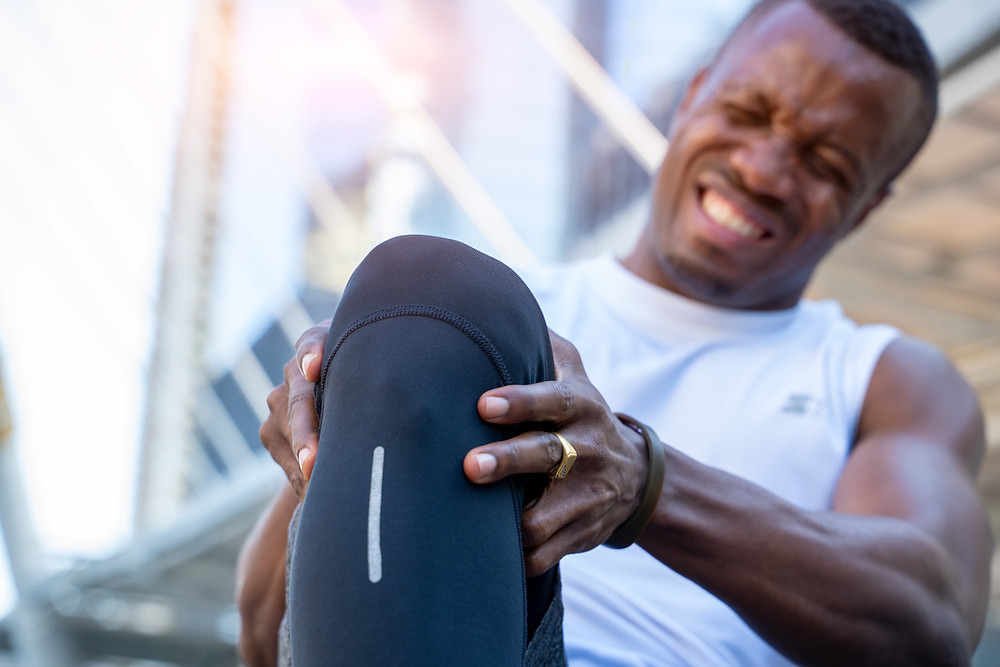 African American male athlete with knee pain