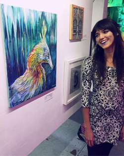 Artist Monique Boileau standing next to her painting of a Phoenix at Garage Gallery in Los Angeles
