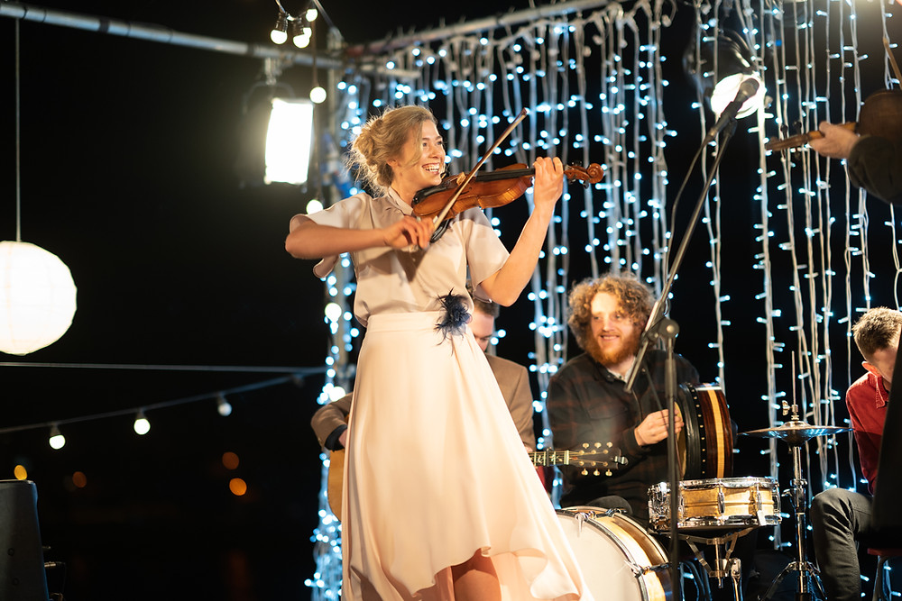 A young woman in a white dress plays a violin on stage, behind is a man playing a drum, with small light strands dropping from above