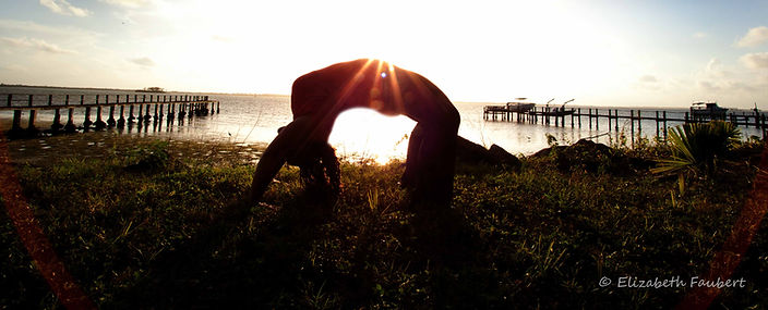 Nicole Longwell doing Yoga with the sun and the sea in the background