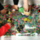 Toddlers playing with an interactive sensory bin.