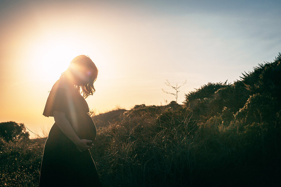 Pregnant Woman holds her belly on a grassy hill at sunset.