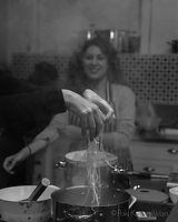 Cooks hands releasing ramen noodle into steaming pot - photograph by Pak Keung Wan