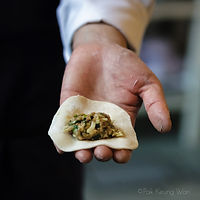 A chef's hand holding gyoza filling on wrap - photograph by Pak Keung Wan