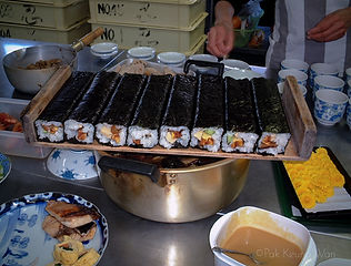 Roll sushi uncut on wooden tray - photograph by Pak Keug Wan