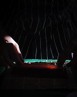 A pair of hands place a piece of tuna on a sheet of nori - photograph by Pak Keung Wan