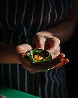 Temaki sushi in sunlit hands - photograph by Pak Keung Wan