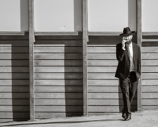 Jewish man on phone in front of wall.jpg