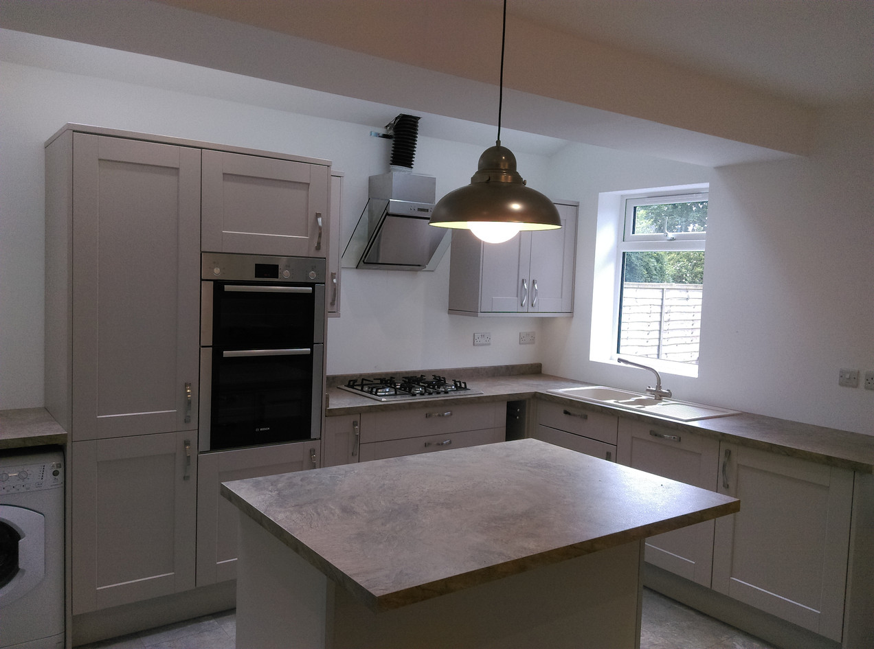 Grey kitchen installation with marble flooring