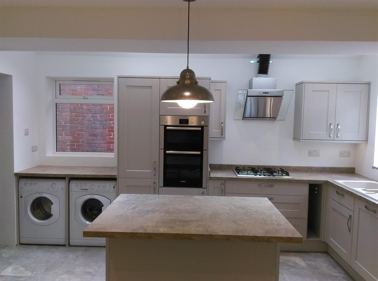 Grey kitchen installation with marble flooring